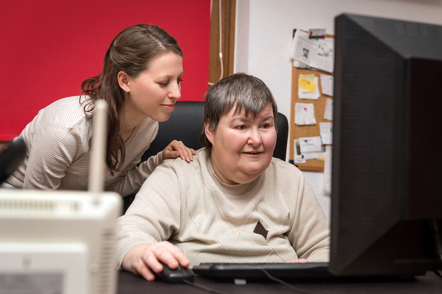 Carer supporting client to use the computer to improve Independence