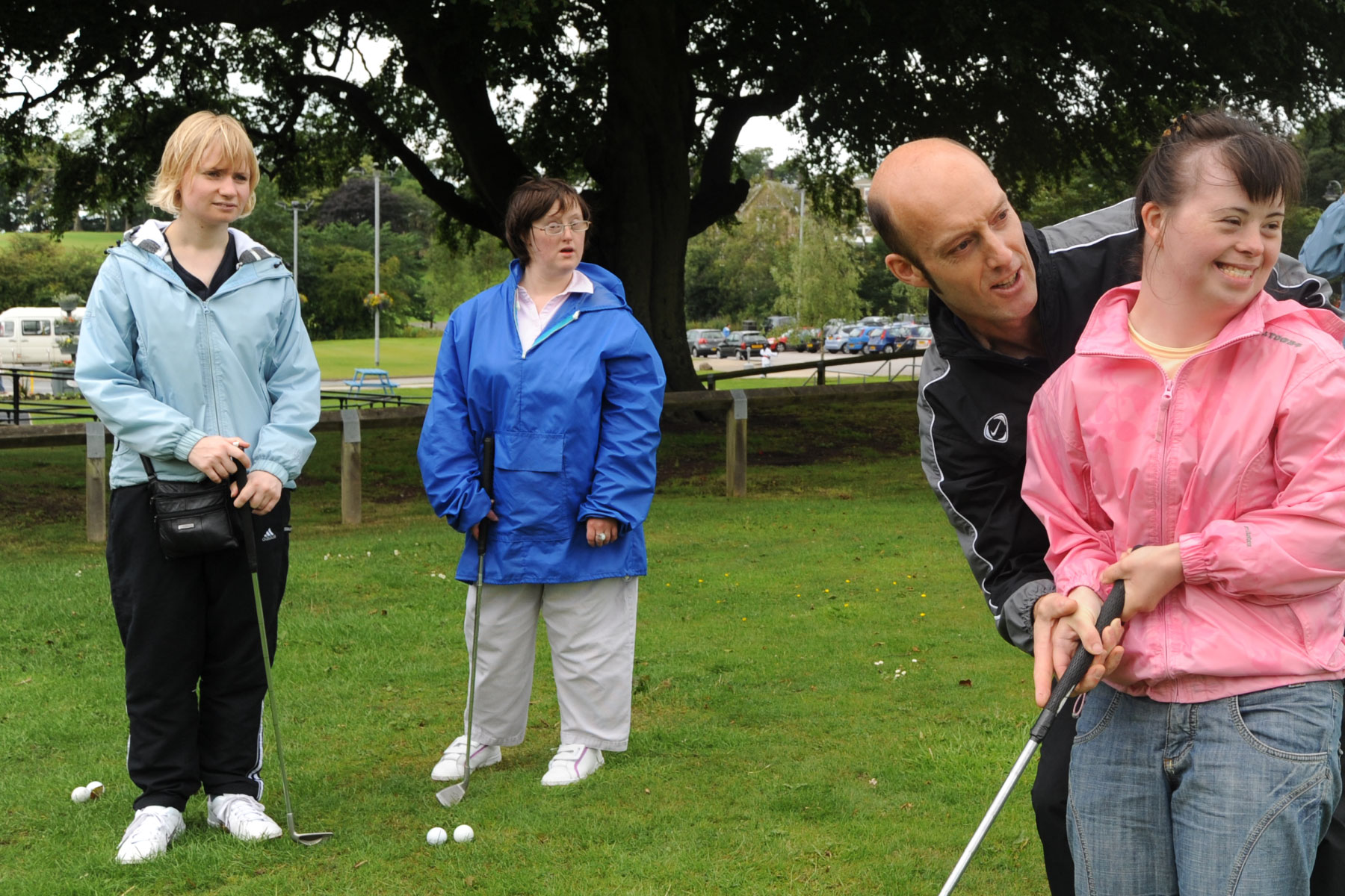 Friendly care worker helps mentally challenged clients be more active with sports